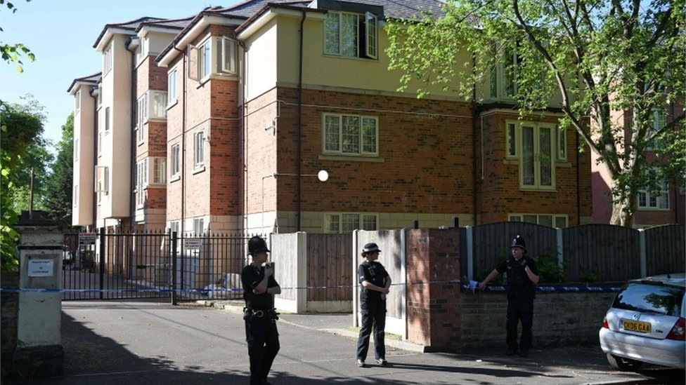 Police standing outside address searched in Whalley Range, Manchester