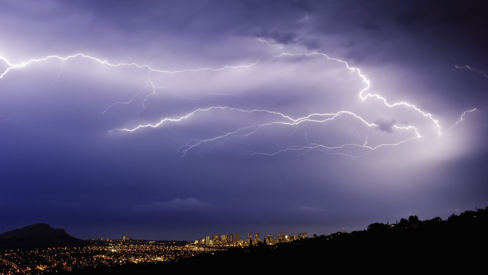 Lightning bolts over a city in a valley at night