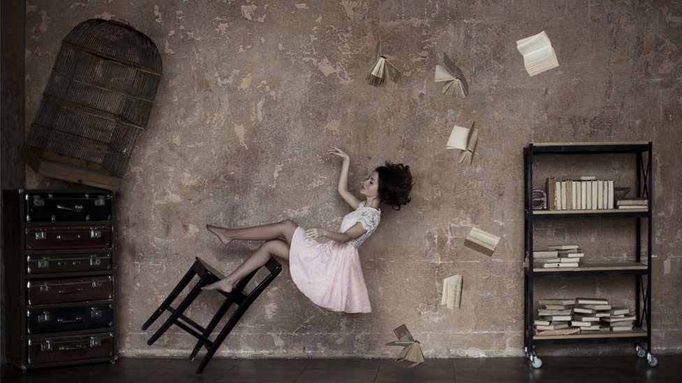 Dreamy composition of a young woman floating in a dusk pink room, with a tilted chair, flying books and a birdcage