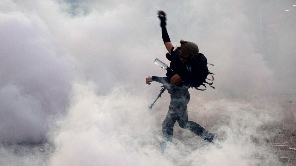 A protester throws bricks at the police after they fired tear gas during a general strike in Hong Kong on 5 August 2019