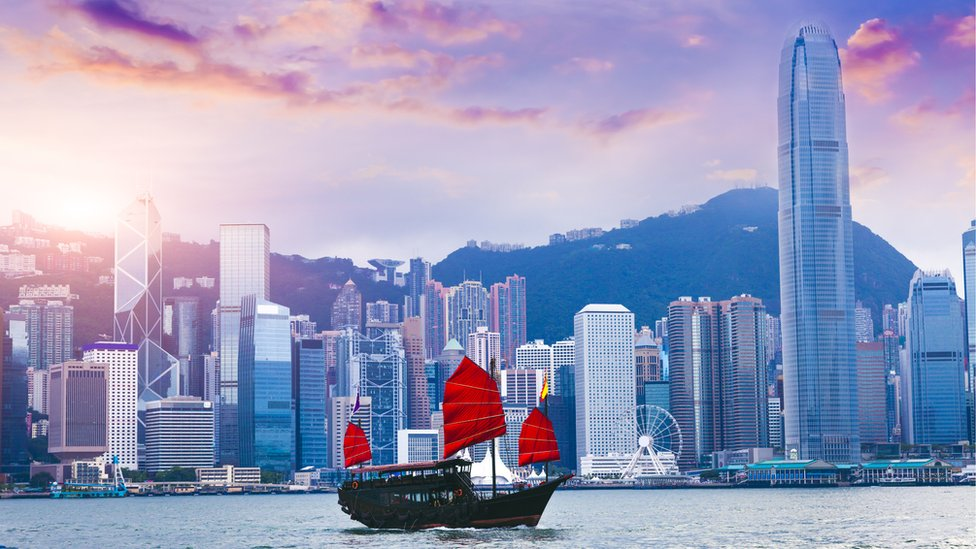 A sailboat travels past Hong Kong Victoria Harbour at sunset (stock picture)