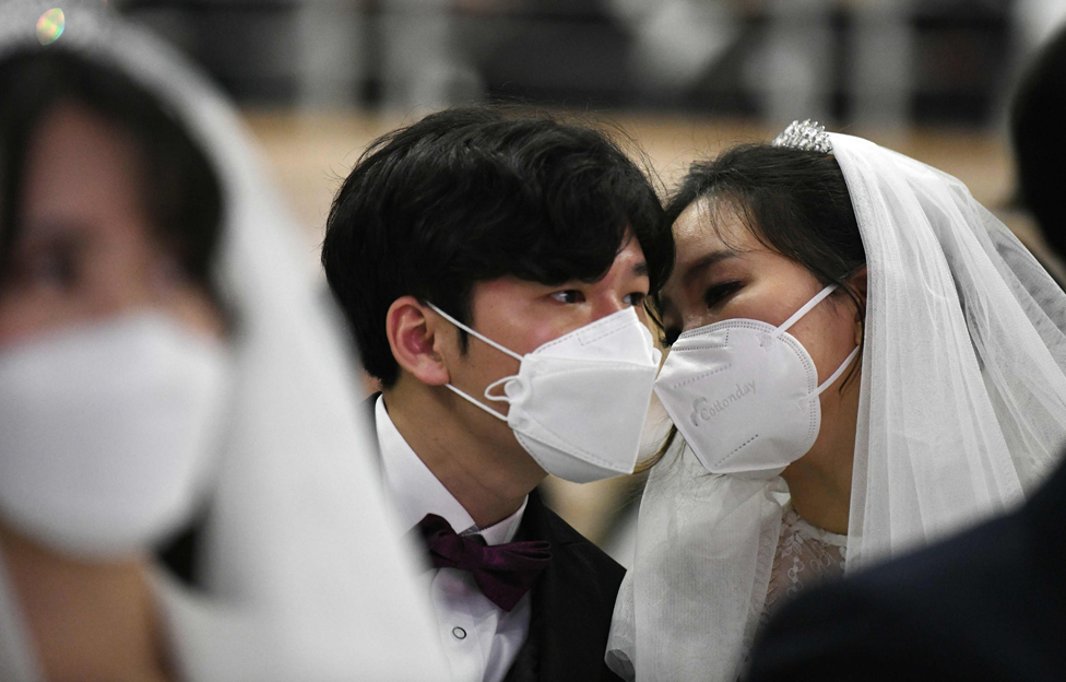 A masked couple share a moment during a mass wedding ceremony organised by the Unification Church in Gapyeong